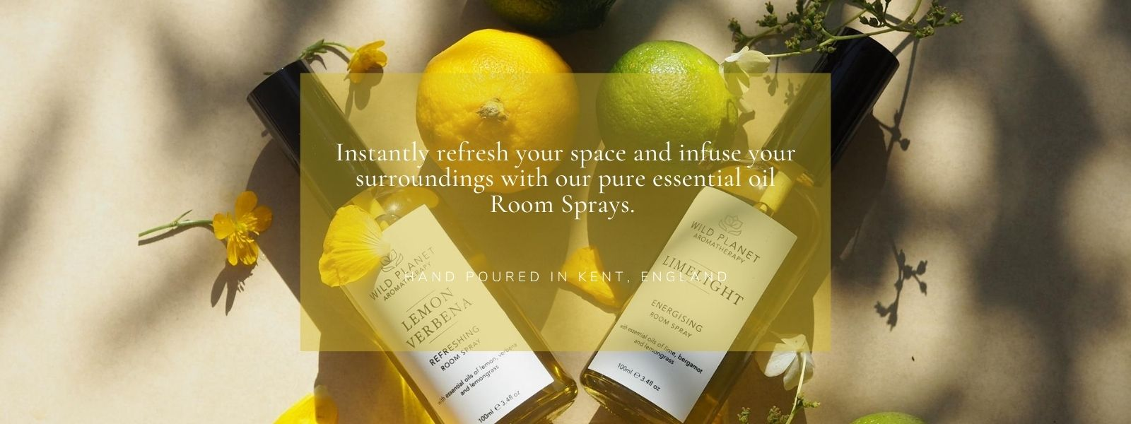 Lemon Verbena Room Spray and Limelight Room Spray next to fresh lemons and limes and flowersby Wild Planet Aromatherapy