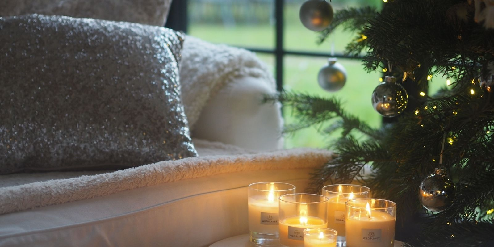 Lit scented candles next to Christmas tree and white sofa by Wild Planet Aromatherapy