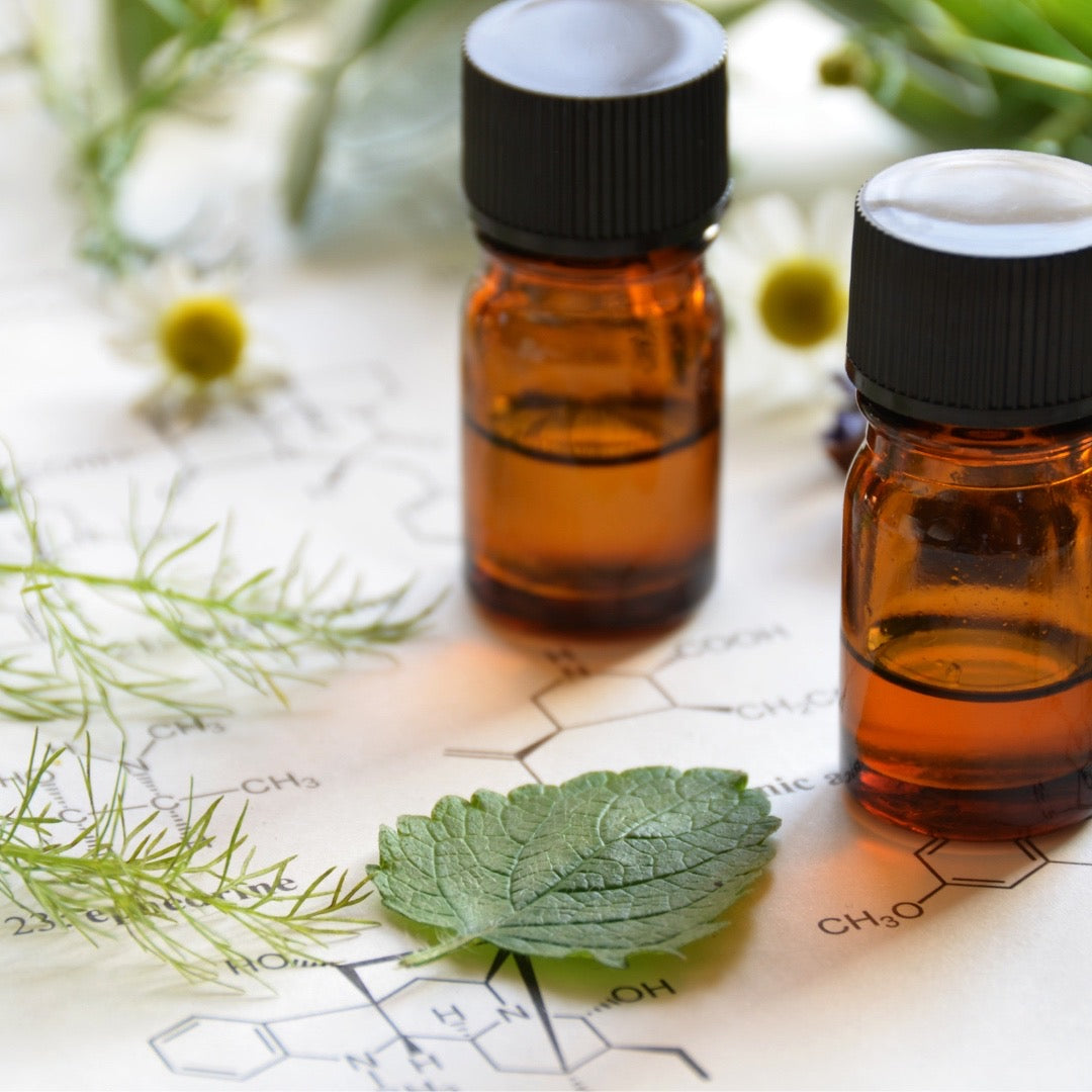 Amber glass bottles of essential oils on white paper with chemical formulas and fresh herbs by Wild Planet Aromatherapy