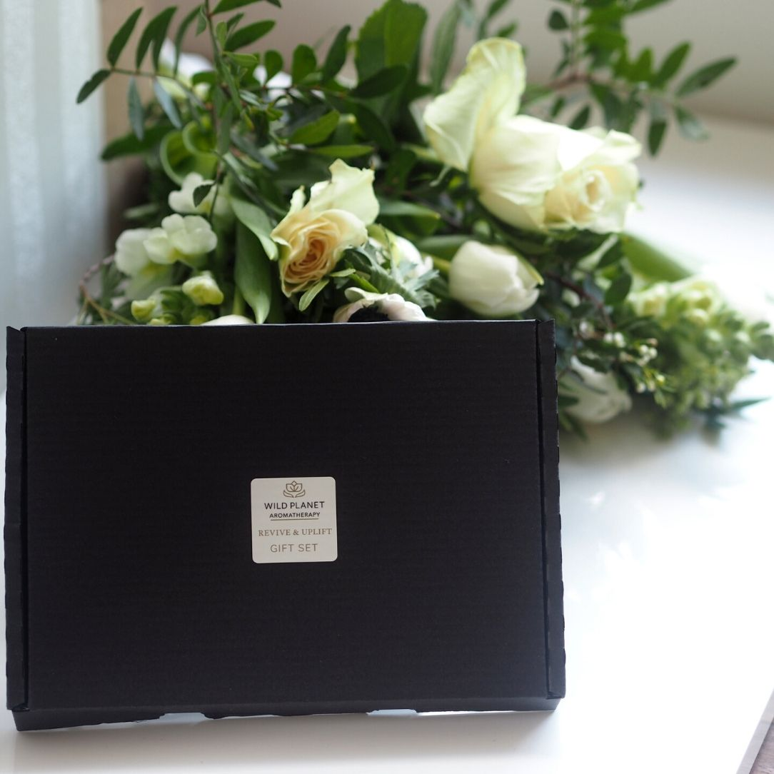Revive and Uplift Luxury Letterbox Gift next to fresh flowers by Wild Planet Aromatherapy