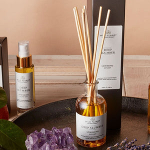 Deep Slumber organic reed diffuser bottle and reeds with amethyst next to black box on tray