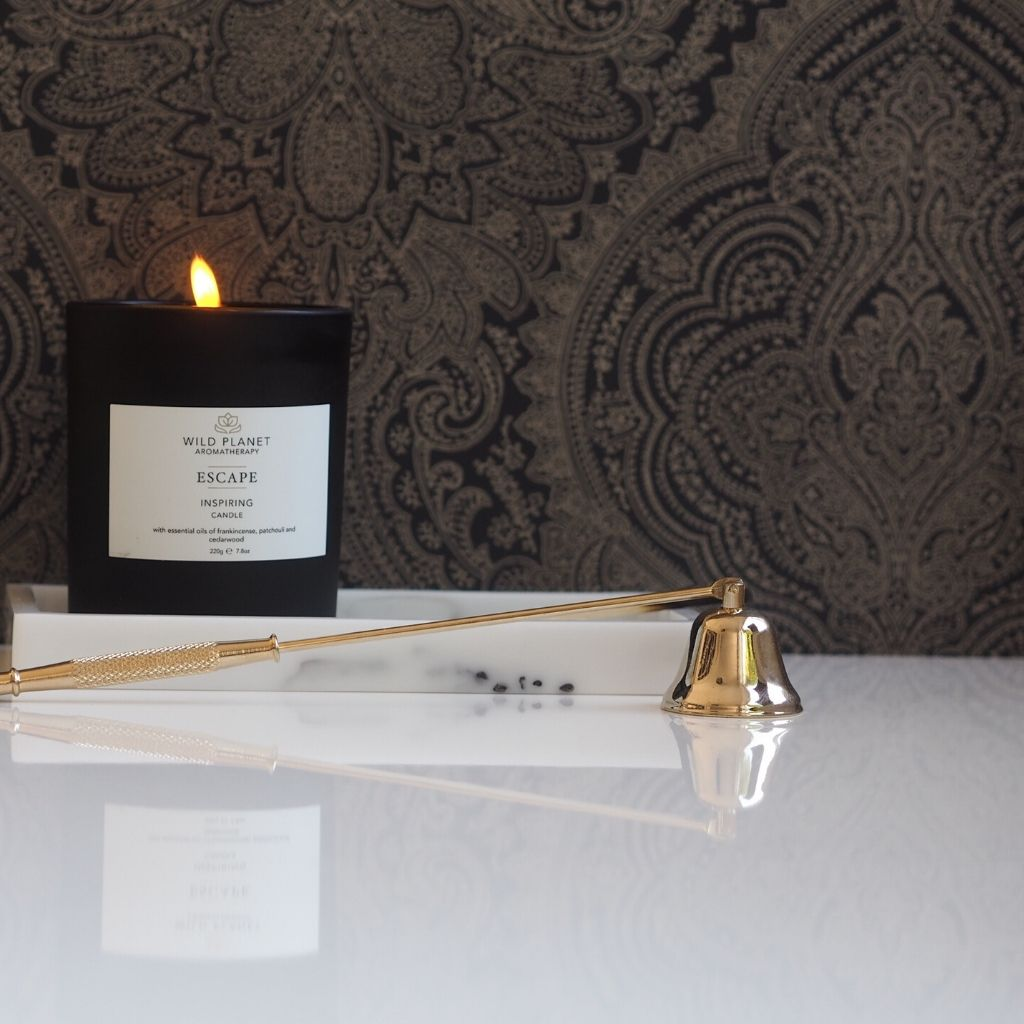 Matt black glass Escape Meditation Candle on marble tray next to gold candle snuffer