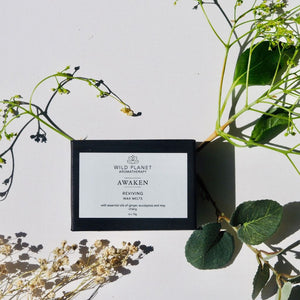 Awaken reviving luxury wax melts in black box next to flowers and eucalyptus leaves