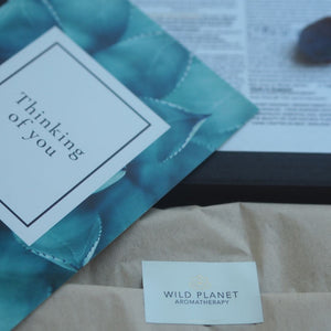 Opened letterbox gift with tissue paper, sticker, Thinking Of You card by Wild Planet Aromatherapy