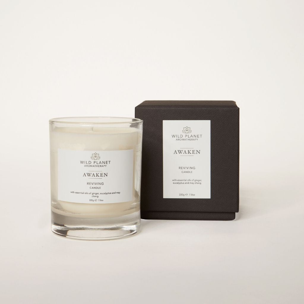 Clear glass Awaken aromatherapy candle next to black branded box with ginger, grapefruit, eucalyptus