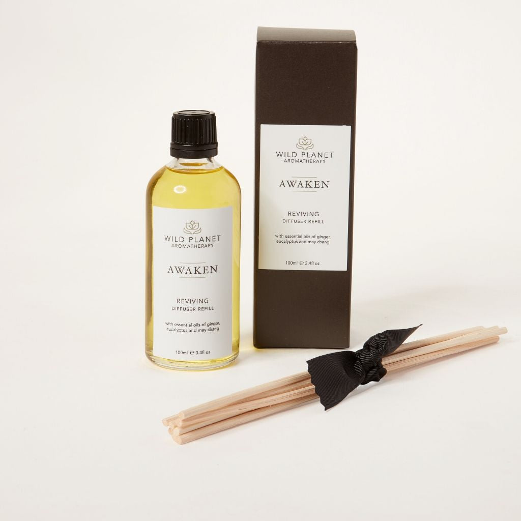 Natural diffuser refill bottle, next to b0x reed sticks tied with ribbon, eucalyptus and ginger