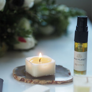 Lit tea light, Revive Aura Spray next to fresh flowers by Wild Planet Aromatherapy