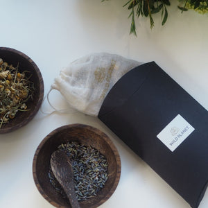 Opened Lavender and Chamomile scented sachet with muslin bag next to bowls of lavender and chamomile