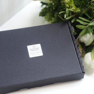 New Mum Letterbox Gift next to fresh flowers by Wild Planet Aromatherapy