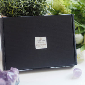 Deep Sleep Letterbox Gift next to fresh flowers and amethyst crystals by Wild Planet Aromatherapy