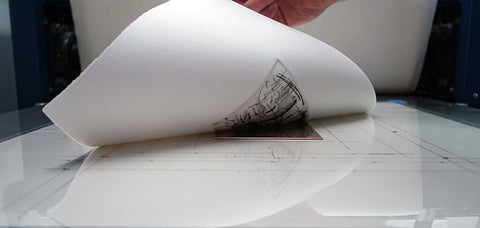 printmaker hand lifting paper from plate after printing