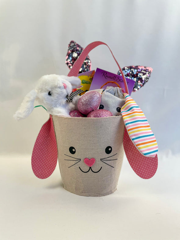 Pink Bunny Basket includes:   Pink bunny fabric basket that can be reused  Russell Stover cookies and crème chocolate bunny - Cookies and crème cookie pieces in white fudge   Sour Patch Kids Bunnies or Warheads Chewy Bunnies (please note candy variety varies)  Stuffed bunny animal  Glitter sequent bunny hear headband (please note bunny sequent color will vary pink or purple)  Bunny canvas bag with floppy ears filled with candy variety  Glittery eggs with Hersey's variety chocolate   Burlap bunny package dec