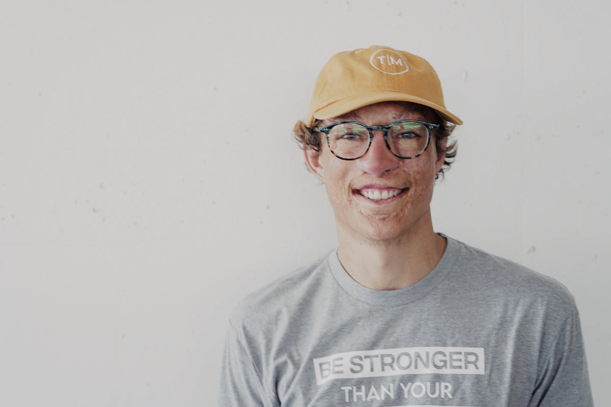 Marius Woodward with gray shirts green glasses and a yellow hat