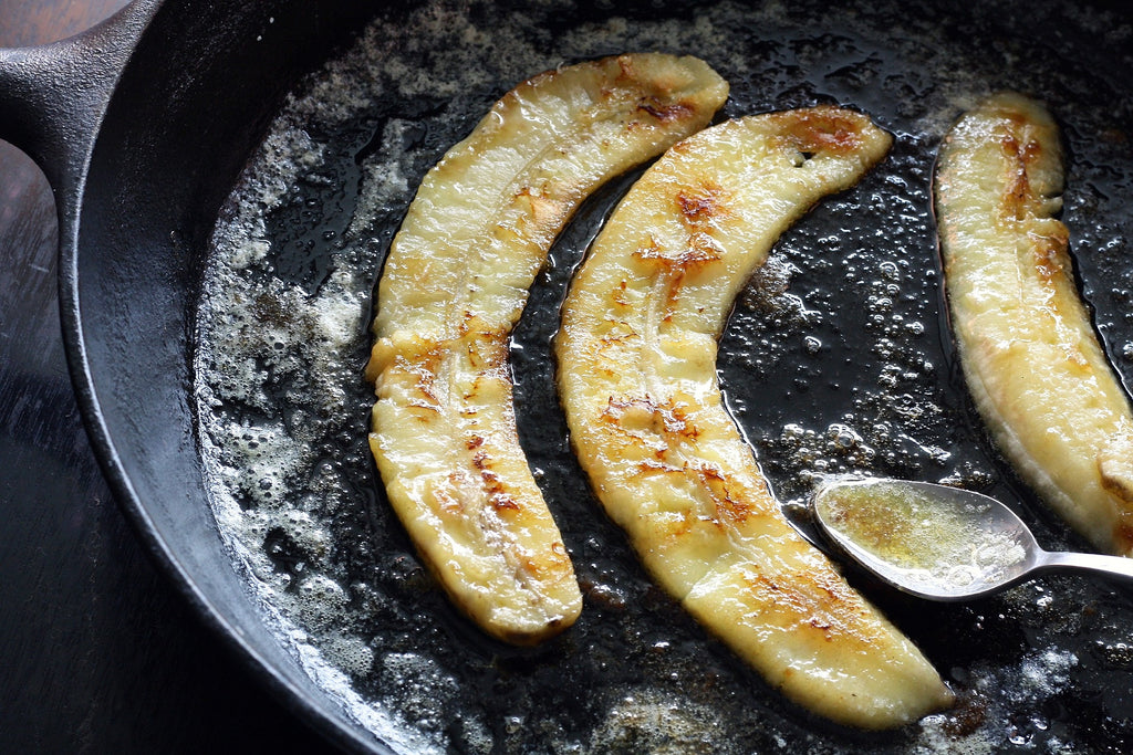 sliced bananas being fried in butter in a cast iron pan