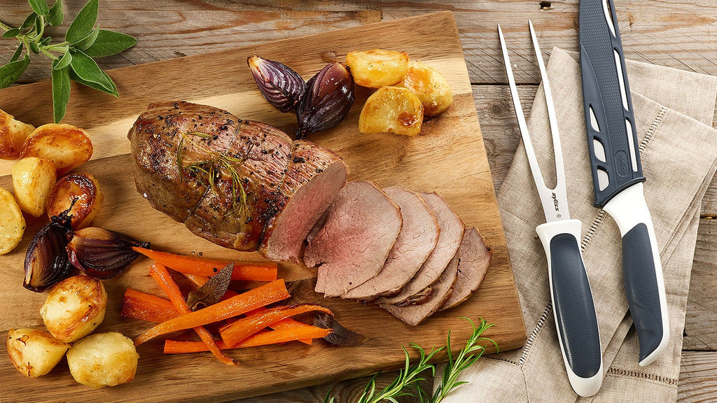 carving knife and fork next to a cut of beef and roast vegetables