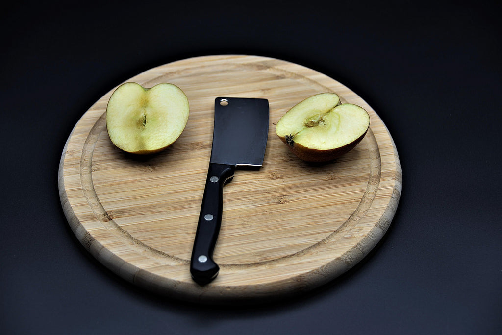 nakiri knife with apple on wooden chopping board