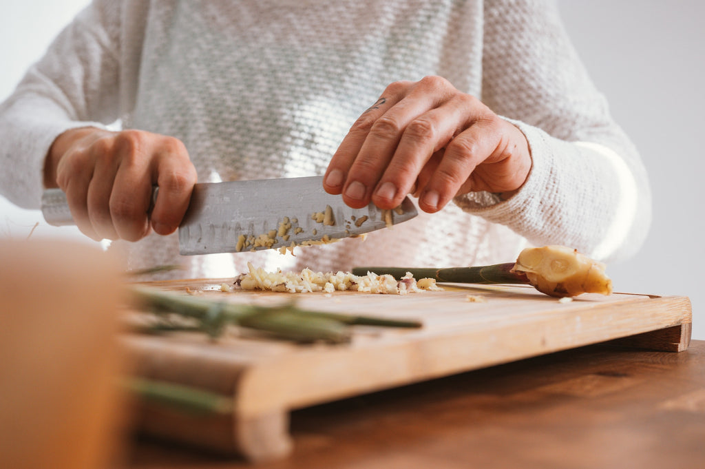 person chopping garlic with a knife not a garlic press