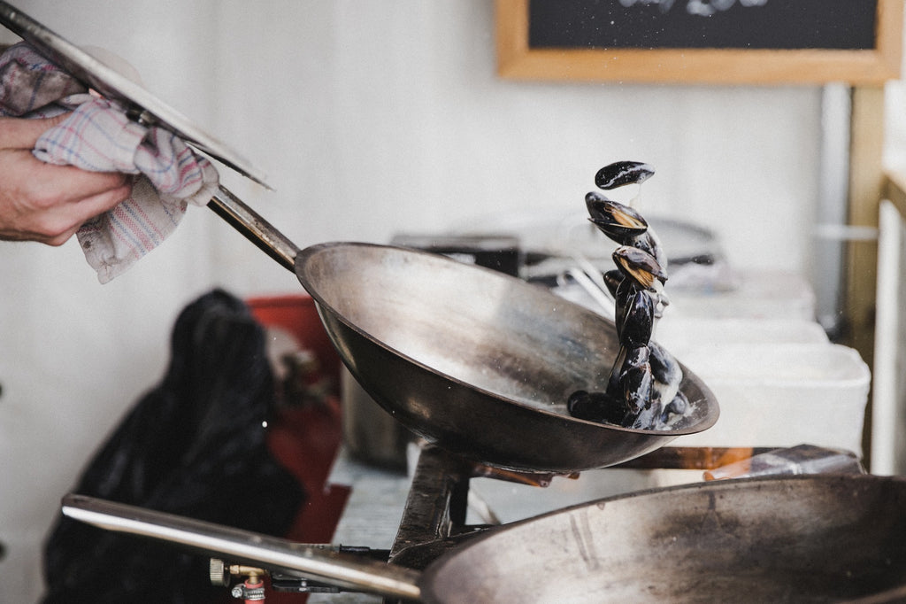 person holding a steel pan frying mussels