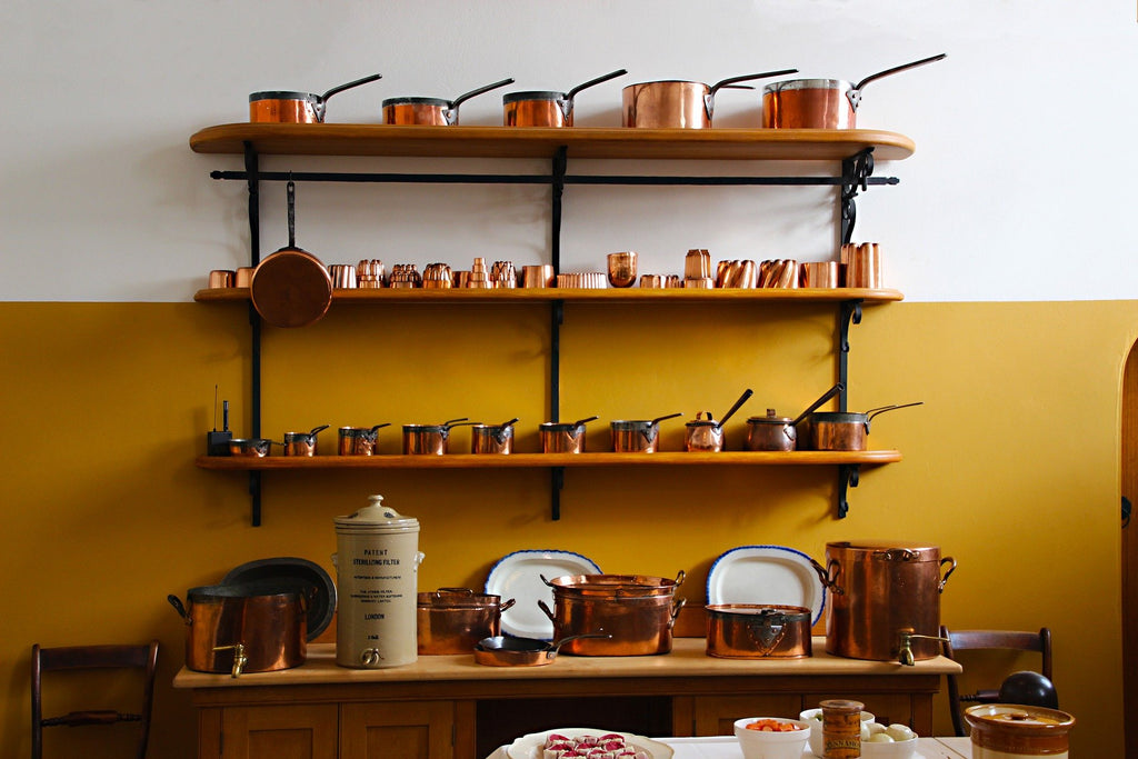selection of copper cookware on shelves in a kitchen