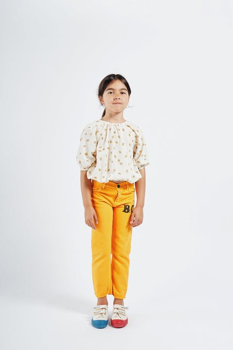 bobo choses ss20 A Dance Romance Daisy peasant Blouse for kids model picture girl wearing white with yellow floral print blouse and yellow trousers 12001058 FRONT