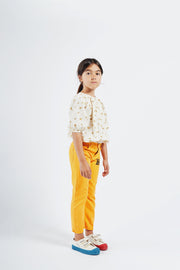 bobo choses ss20 A Dance Romance Daisy peasant Blouse for kids model picture girl wearing white with yellow floral print blouse and yellow trousers 12001058 SIDE