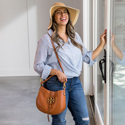 Fashionable woman wearing a floppy beach hat, blue top and holding a tan Tory Burch handbag.