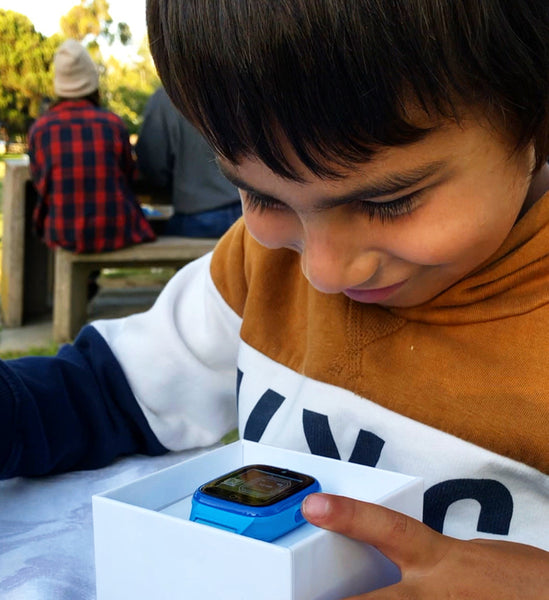 Child smiling at kids smartwatch in box