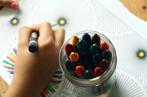 A kids uses crayons to create art