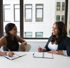 Two women sitting at a desk with notepads and pens