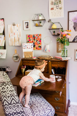 Toddler reaching up for desk looking mischevious