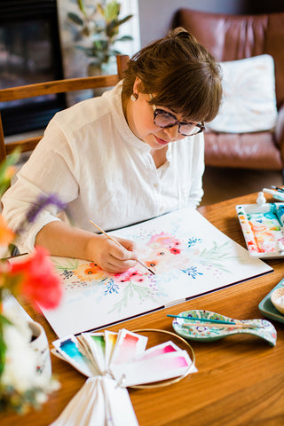 Kate painting florals on a large canvas