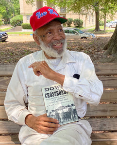 James Meredith smiling on shaded park bench wearing bright red baseball cap with New Miss embroidered in blue script