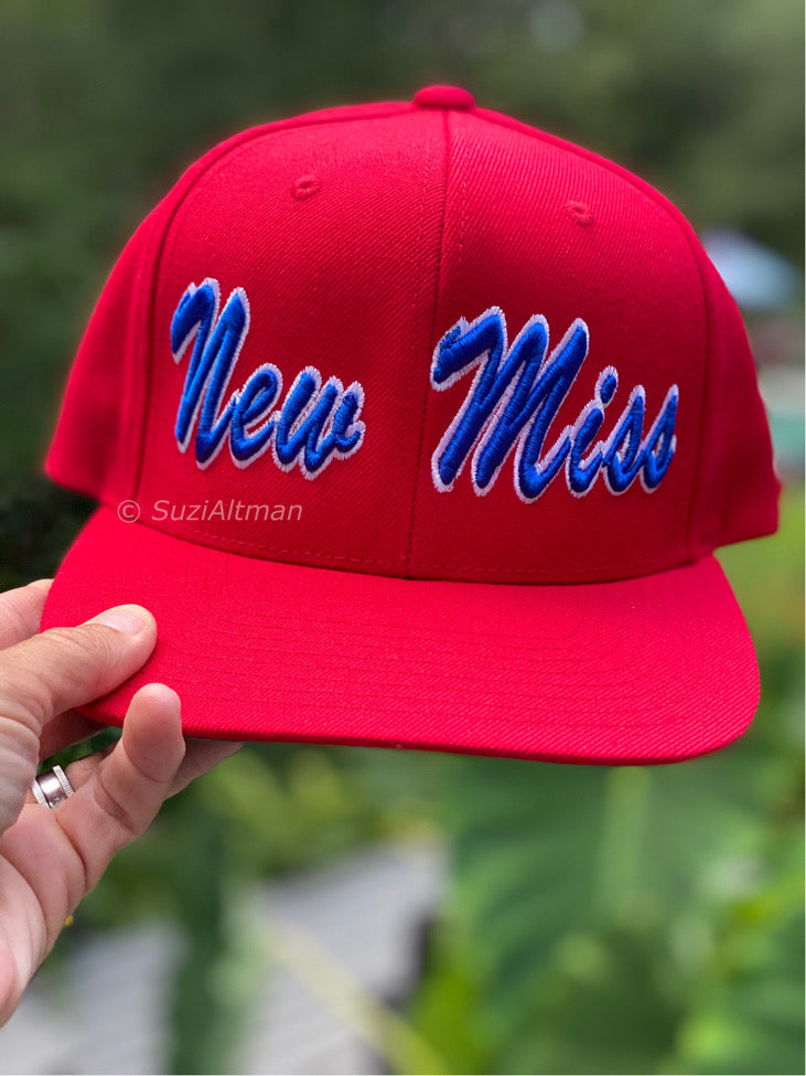 Bright red adjustable baseball cap with thick embroidery words in blue script New Miss