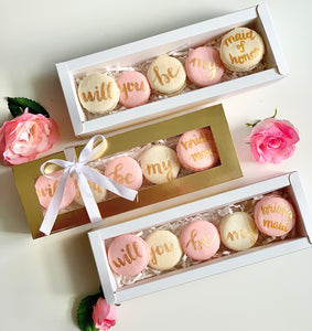 """Will you be my bridesmaid/maid of honor"" proposal macaron set. Packaged in a shiny gold box and tied off with a bow."