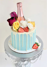 Load image into Gallery viewer, Champagne Cake with a sky blue exterior, glossy white drip, roses surrounding with strawberries