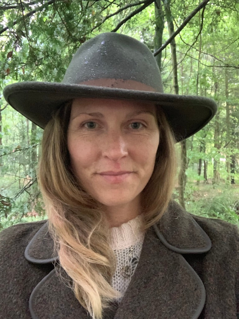 Ruth Rands, founder and CEO of Herd Wool and Wear in a felt hat in a forest