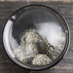 Magnifying glass with pyrite stones
