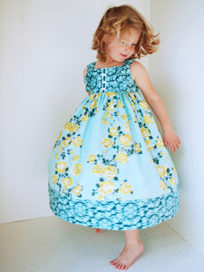 blonde haired girl twirling in an handmade blue and yellow floral knot dress