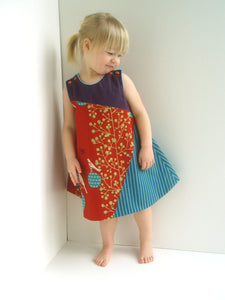 little girl on white background wearing a handmade asymmetric a-line dress made from three japanese fabrics.  the colors are rust, aqua, and eggplant purple.
