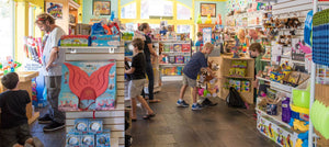 Image of toy store filled with unique hard to find toys and filled with happy playing children. In the foreground a father enjoys building toys with his son.