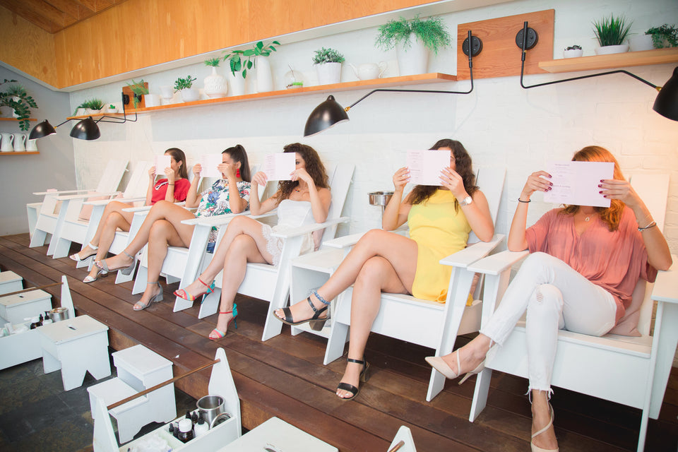 Five teen girls sitting in white chairs with their legs crossed each reading a tablet in front of their faces.