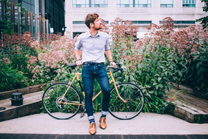 A man in a dress shirt and jeans leaning against a bicycle in front of a large flowered bush.