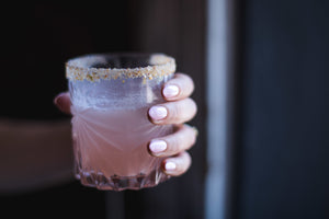 Woman with painted nails holding a whiskey glass with a pink drink inside and a garnished rim.