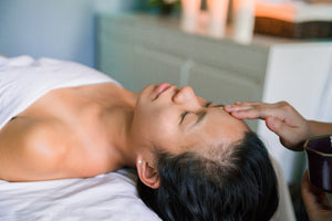 A woman laying face up on a massage table with a white towel draped over top of her with another person touching her forehead.