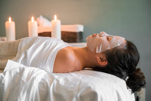 Woman laying on a massage table with a facial mask on with three candles in the background.
