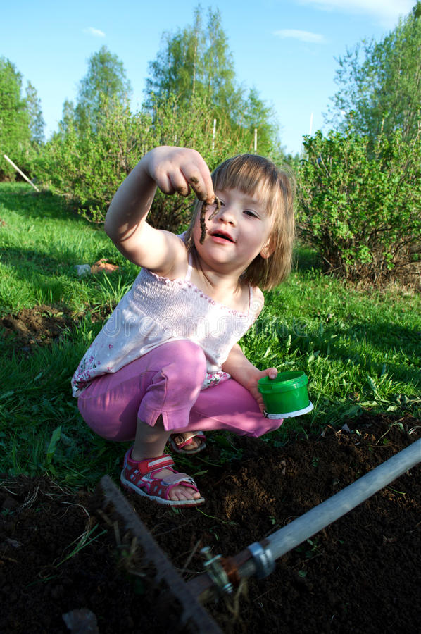 Young girl holding a worm in a garden