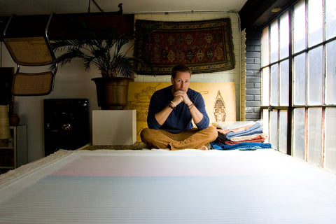 Portrait of the Artist in his mezzanine work area with a recently  finished piece laying in front