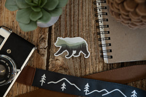 Bear Landscape Sticker on wood background with notebook camera and succulent