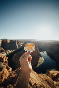 Hand holding out Wildtree Horseshoe Bend sticker at Horseshoe Bend Arizona