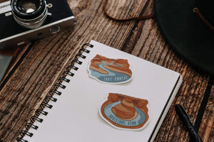 Wildtree Lake Powell Sticker and Horseshoe bend sticker sitting on notepad